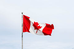 Canadian Flag Flying Under Clouds Stock Photos