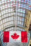 Canadian flag and glass roof in the background Stock Photography