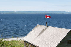 Canadian flag in high wind. Located in Forilon National Park near Gaspe, Quebec, Canada.  Gaspe is known for its high winds Royalty Free Stock Images