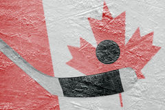 Canadian flag and hockey puck with a stick Royalty Free Stock Images