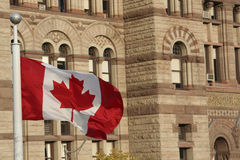 Canadian flag. With the old Toronto city hall on Nathan Phillips square in the background Stock Image