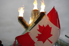 The National Flag of Canada with Olympic flame Stock Photos