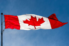 Canadian Flag over beautiful blue sky Royalty Free Stock Image