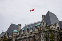 Canadian flag over Empress Hotel, Victoria, Canada. Canadian flag flying over the Fairmont Empress hotel in Victoria, British Columbia, Canada on overcast day Royalty Free Stock Photo