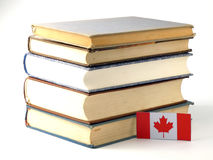 Canadian flag with pile of books on white background royalty free stock photos