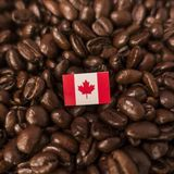 A Canadian flag placed over roasted coffee beans stock photo