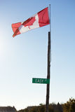 Canadian flag on a post blowing in the wind. Canadian flag on a post with 'Easy street' sign beneath it Royalty Free Stock Images