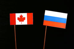 Canadian flag with Russian flag isolated on black Stock Images