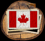 Canadian Flag on Section of Tree Trunk. Flag of Canada in a old photo frame on a section of tree trunk isolated on black background Royalty Free Stock Image