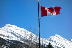 Canadian National Flag and Rocky Mountains. Canadian Flag with Snowy Rocky Mountain Tops of Banff National Park in the Background Royalty Free Stock Photography