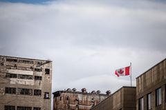 Canadian flag waiving in front of an old industrial zone made of abandoned silos, factories and warehouses on Montreal port, Quebe. Picture of abandoned silos royalty free stock images