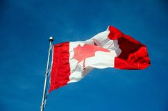 Canadian flag waving in the sky Royalty Free Stock Photography