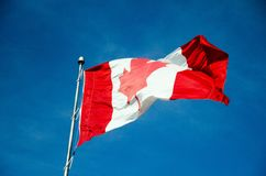 Canadian flag waving in the sky Stock Image