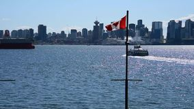The Canadian flag waving in the sky./seabus Ver.1. The Canadian flag waving in the sky, with the Harbour Tower visible in the background. The focus is on stock video footage