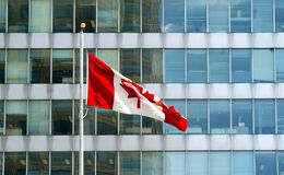 Canadian flag in the wind. In the city of Montreal in front of Canada Revenue Agency buildings on Renée Lévesque boulevard Stock Photo