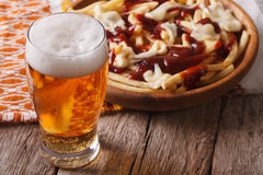 Canadian food: beer and fries with sauce close-up. horizontal. Canadian food: beer and fries with sauce close-up on the table. horizontal Royalty Free Stock Photos