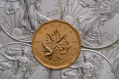 Canadian Gold Maple Leaf ontop of American Silver Eagles Stock Photo