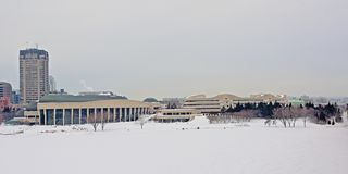 Canadian history museum  on a cold winter day with snow. Modern architecture of the Canadian history museum in a park with bare and spruce trees on a cold grey stock image