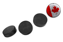 Canadian hockey pucks. Lined up in a row on white background Stock Photo