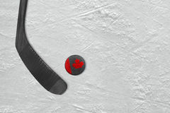 Canadian hockey stick and puck on the ice hockey rink Royalty Free Stock Photography