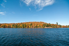 Canadian Lake with Autumn Colours and Blue Sky. The water and shoreline of Lake of Bays in Muskoka, Ontario, Canada with colourful fall leaves and a deep blue Royalty Free Stock Photography