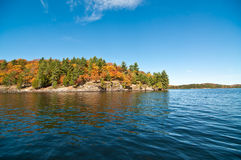 Canadian Lake with Autumn Colours and Blue Sky. The water and shoreline of Lake of Bays in Muskoka, Ontario, Canada with colourful fall leaves and a deep blue Stock Image