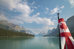 Canadian landscape with mountains, Maligne lake and flag. Albert Royalty Free Stock Images