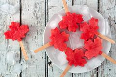 Canadian maple leaf watermelon pops on a plate against rustic white wood. Canadian maple leaf watermelon pops on a plate against a rustic old white wood Stock Photo