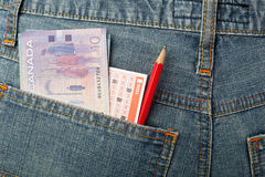 Canadian money and lottery bet slip in pocket Stock Image