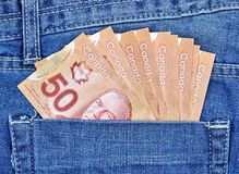 Canadian money in a pocket. Of a blue jeans stock photo