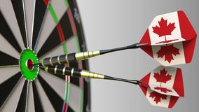 Canadian national achievement. Flags of Canada on darts hitting bullseye. Conceptual 3D rendering. Canadian national achievement. Flags of Canada on darts Royalty Free Stock Photos