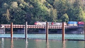 Canadian National (CN)  Freight Train. A Canadian National freight train rumbles across a bridge over the Harrison River channel at Harrison Mills.  Canadian Stock Image