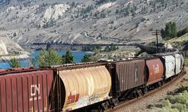 Canadian National (CN) Train near Ashcroft BC. A Canadian National (CN) train pulling boxcars and tankers winds its way along the Thompson River near Ashcroft Royalty Free Stock Images