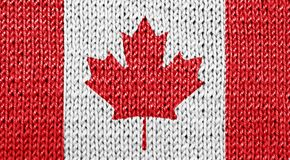 Canadian national flag on knitted background. Front view of Canadian national flag blended on white knitted background stock photography