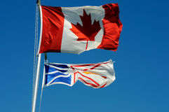 Canadian & Newfoundland Flags. The Flags Of Canada And Newfoundland And Labrador Flying From A Flagpole stock images