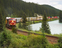 Canadian Pacific Railway. Freight train moving along Bow river in Canadian Rockies. Alberta, Canada Royalty Free Stock Images