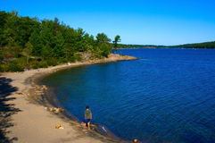 Canadian Park. A teenager boy walking barefoot on the beach of a deep blue lake in a park Royalty Free Stock Photography