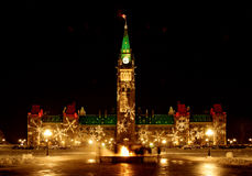 Canadian Parliament at Christmas. Parliament of Canada lit up for the holidays, with eternal flame in foreground; perspective corrected Royalty Free Stock Photos