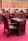 Canadian Parliament: the Senate. The Senate (the Red Chamber) of the Canadian Parliament in Ottawa, Canada. The view on a standalone desk in the middle of the Stock Image