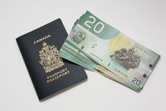Canadian passport with dollar bills Royalty Free Stock Images