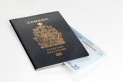 Canadian passport with 20 Euros banknote. Entered into passport pages, on a white background Stock Photos