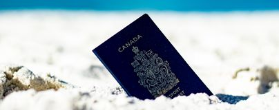 A Canadian passport lying in the sand at the beach closeup. stock photography