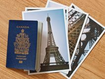 Canadian passport with selection of Parisian travel photos on wo Stock Image
