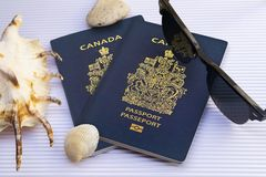 Canadian passports with sunglasses and seashells on white cardboard background royalty free stock photography