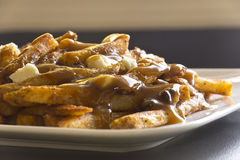 Canadian Poutine, Gravy and French. Canadian cuisine, Poutine, gravy, french fries, and cheese curd Stock Photos