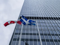 Canadian and Quebec flags in front of a skyscraper stock images