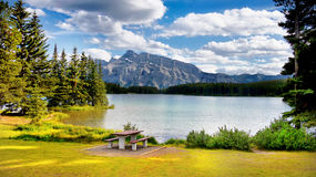 Canadian Rockies, Landscape Lake Mountains. Wooden table and bench at lakeside and mountains scenery. Canadian Rockies. Landscape, Canada Royalty Free Stock Images