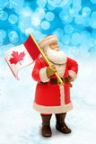 Canadian Santa Claus holding the Canada flag. royalty free stock photography