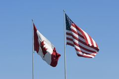 Canadian and US flags. Against a clear blue sky Stock Photos