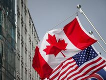 Canadian and USA flags in front of a business building in Toronto Ontario, Canada. Toronto is the biggest city of Canada. Picture of the canadian flag joint royalty free stock photos